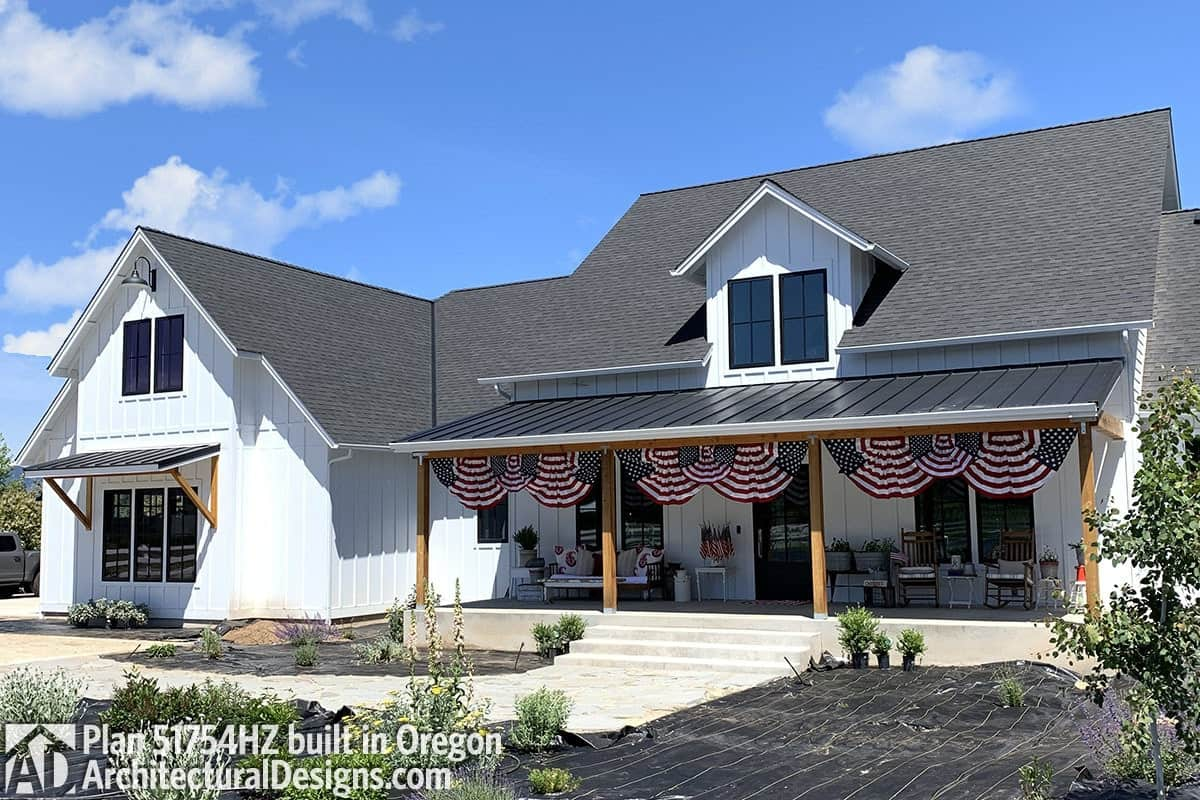 Rustic columns, a large dormer, and decorative flags adorn this home's facade.