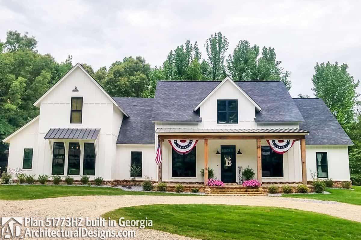 Decorative flags and rustic columns adorn the white modern farmhouse.