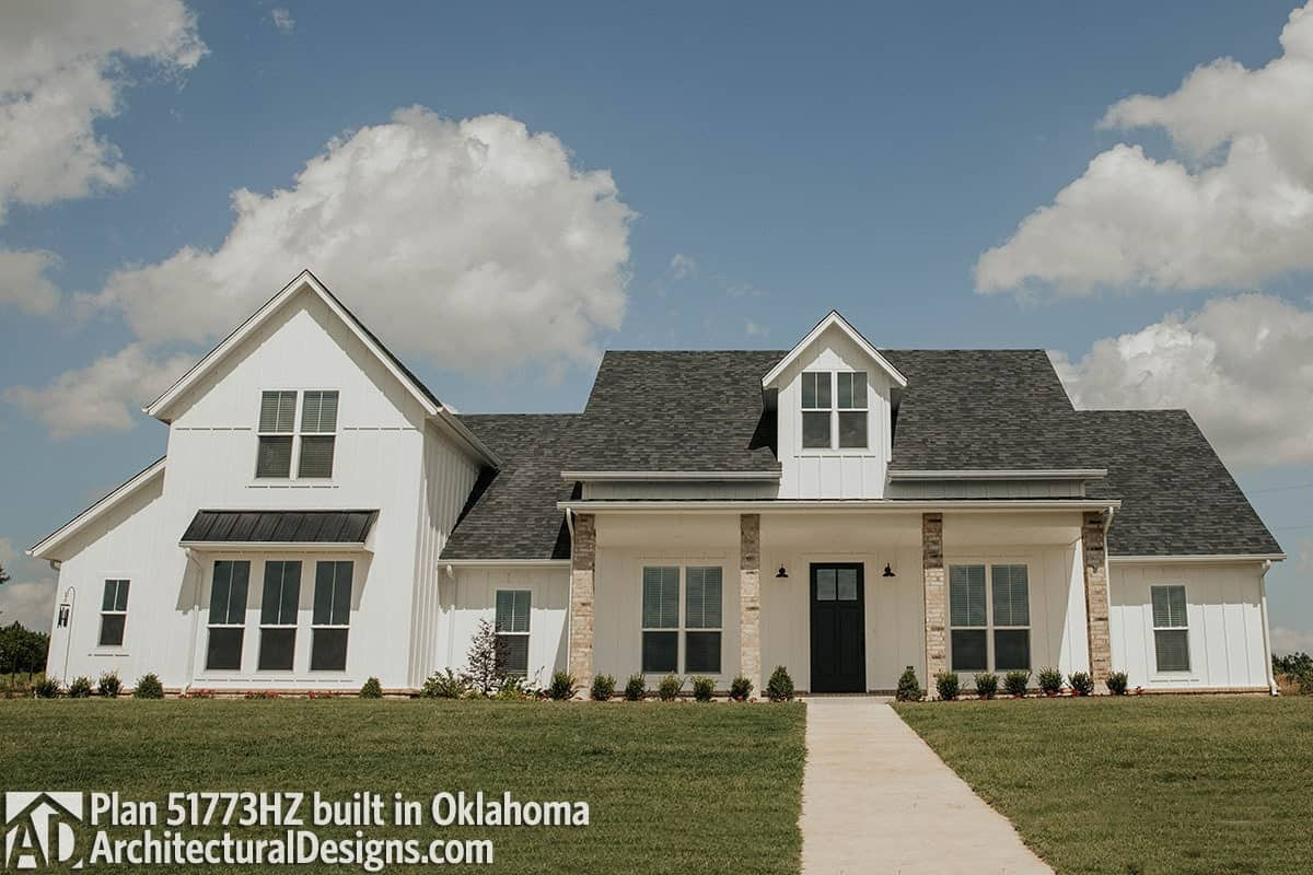 This home has vertical lap siding, stone columns, and a wide porch topped with a shed dormer.