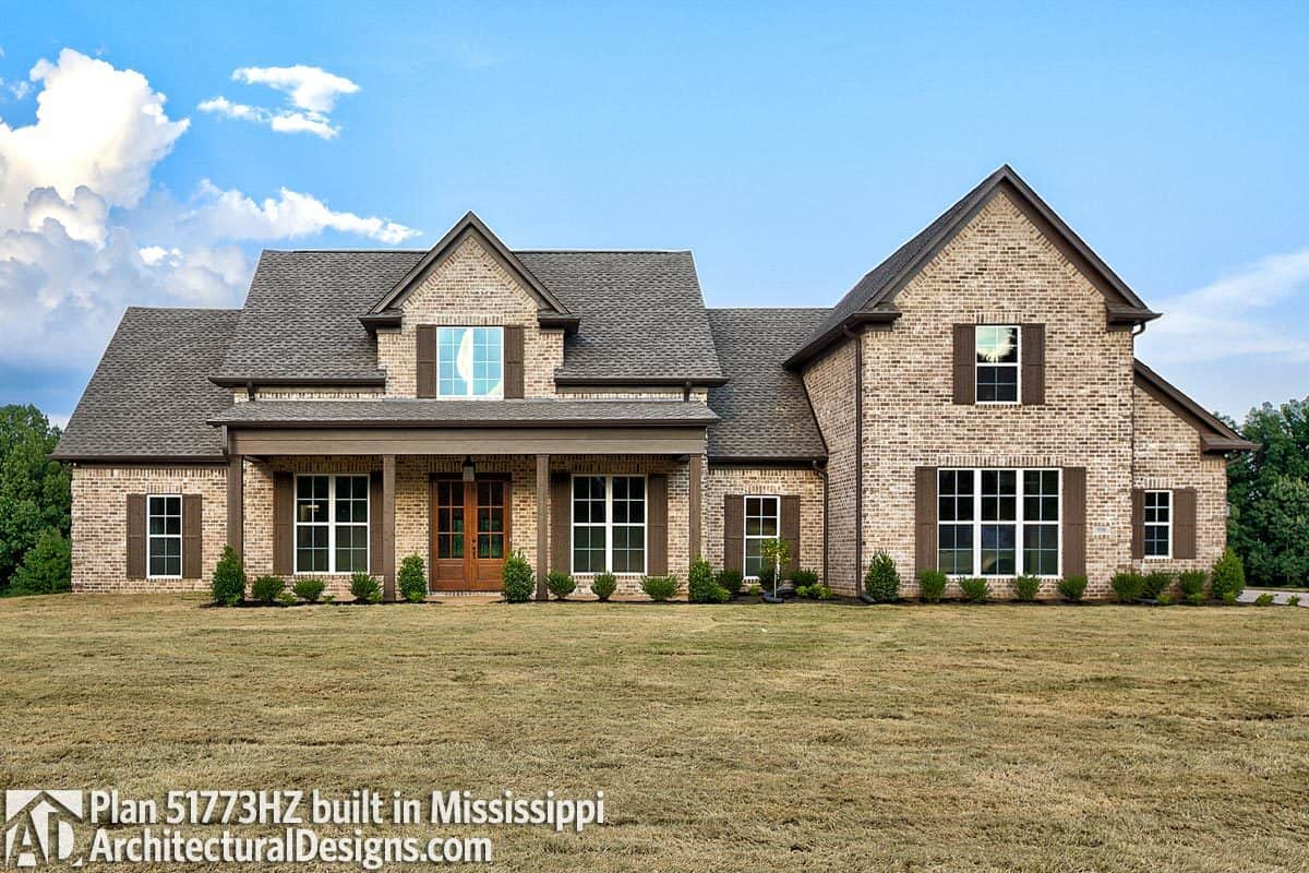 Brick exterior, barn shutters, and tiled roofs embellish this modern farmhouse.