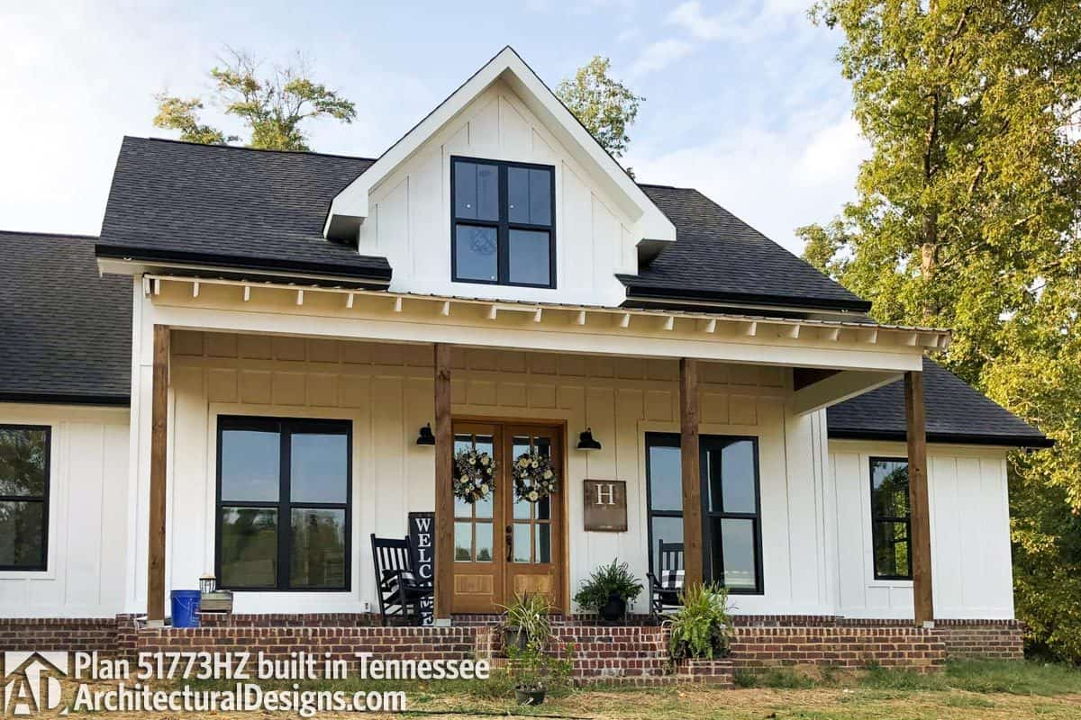 A closer look at the front porch graced by a large dormer, a decorative arbor, and rustic columns.
