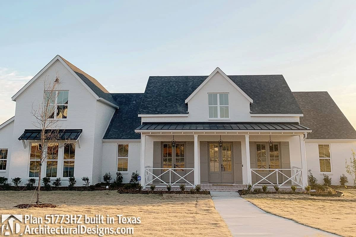 The home features a white siding and a covered porch adorned with three sets of french doors and white railings arranged in a crisscross pattern.