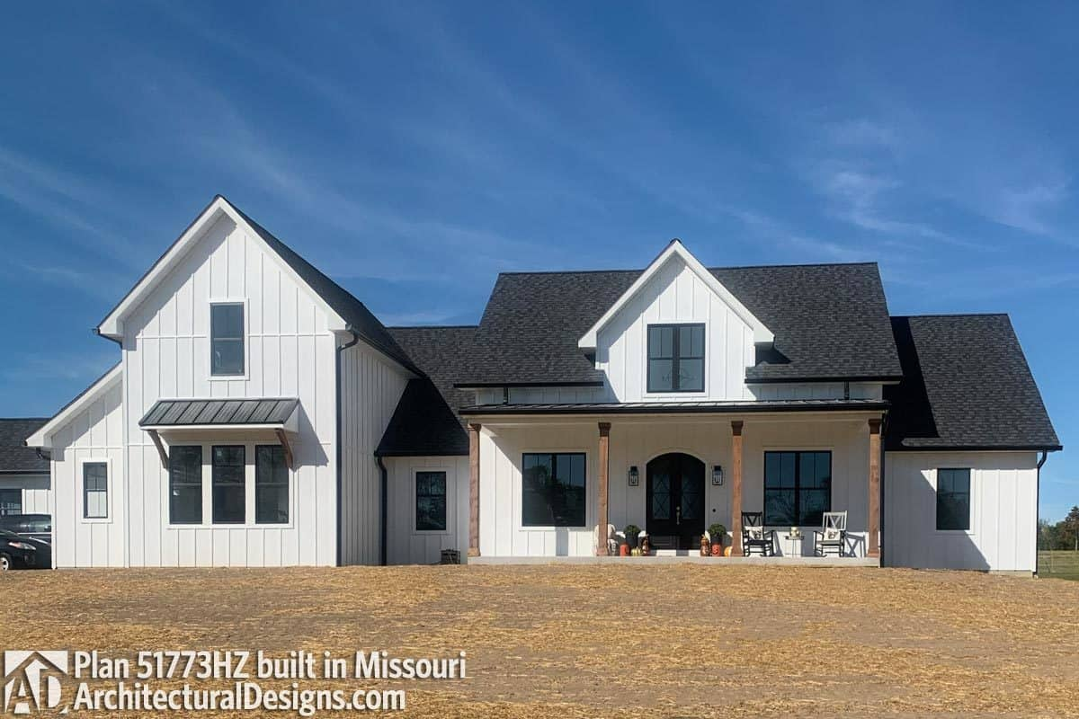 This home has an arched entry door and white board and batten siding contrasted by black-tiled roofs.
