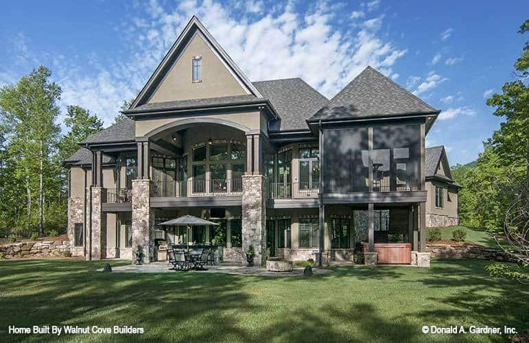 Rear exterior view showing the expansive porches and a screened porch supported by rustic columns.
