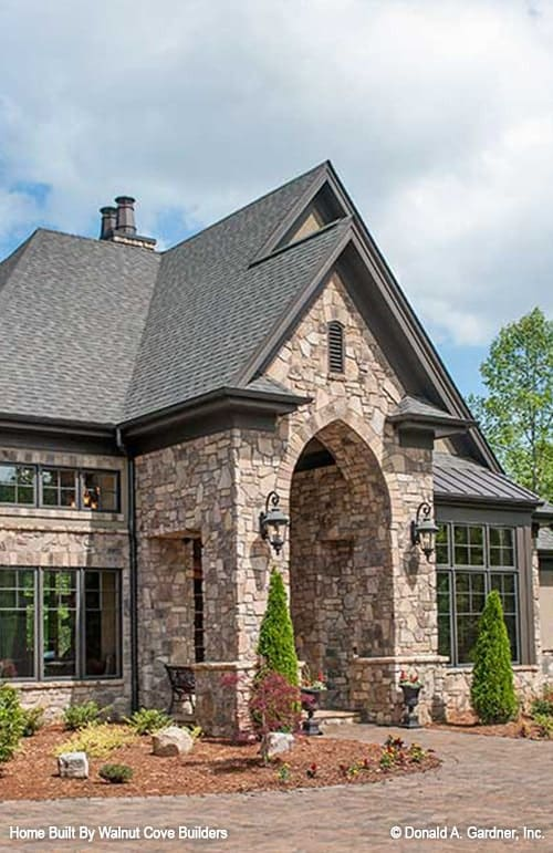 Home entry with a stone archway flanked by outdoor sconces.