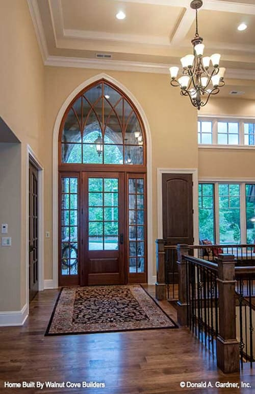 The foyer has a bordered area rug, and a glazed front door topped with an arched transom.