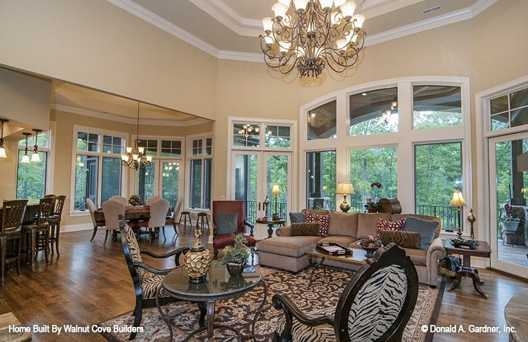 The living room has a brown sectional, zebra round back chairs, metal tables, and an ornate chandelier that hangs from the tray ceiling.