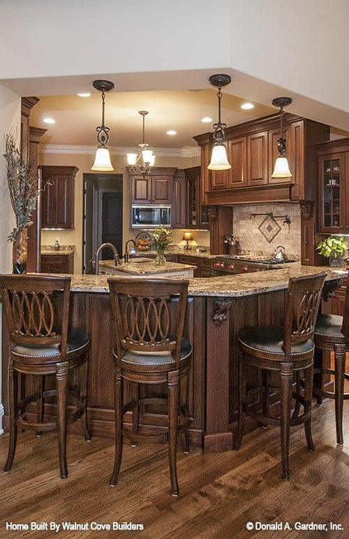 The kitchen is equipped with wooden cabinetry, granite countertops, a center island, and a curved peninsula.