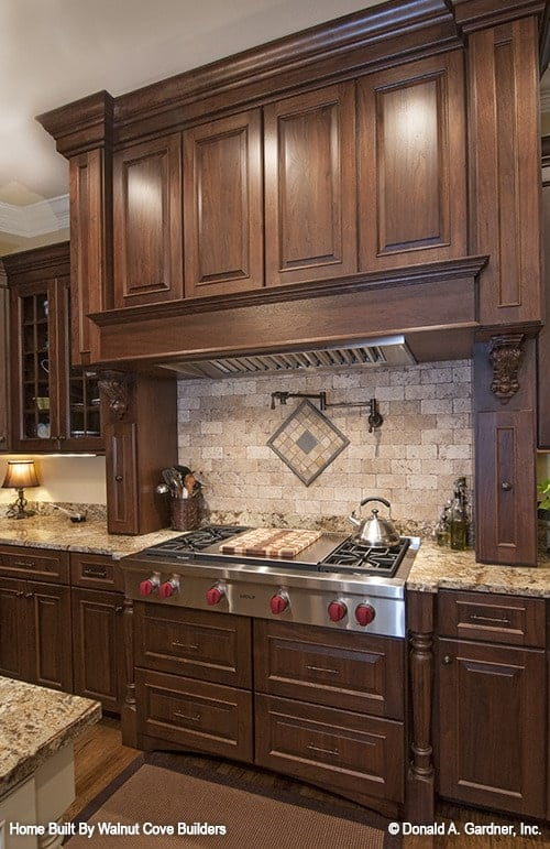 The built-in cooktop is placed against the brick tile backsplash.
