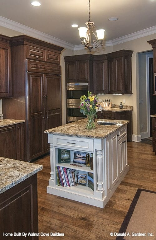 The center island is fitted with built-in shelves and a round sink.