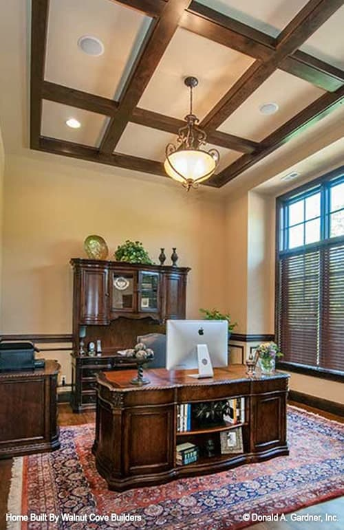 Study with wooden coffered ceiling, dark wood cabinets, and a matching desk that sits on a tasseled area rug.