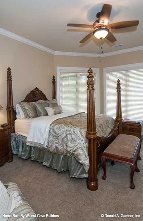 The primary bedroom has beige walls, louvered windows, and a four-poster bed complemented with a cushioned bench.