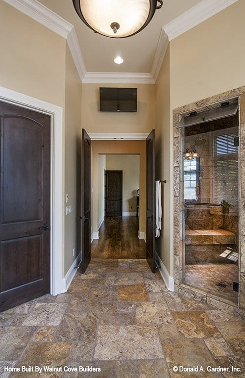 A wooden double door reveals the primary bath with a walk-in shower and a toilet room.A wooden double door reveals the primary bath with a walk-in shower and a toilet room.