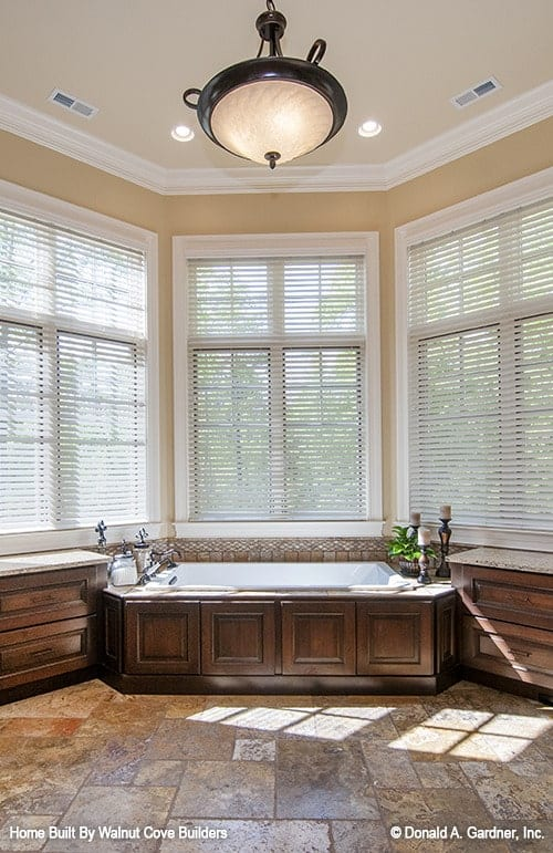 Drop-in bathtub nestled in between the vanities complete the primary bathroom.