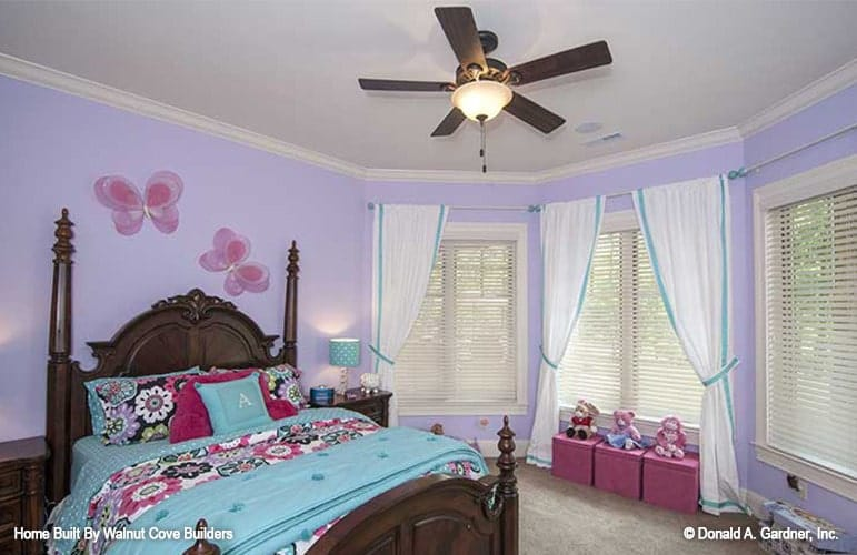 Kid's bedroom with purple walls, dark wood bed, and a bay window dressed in sheer curtains.