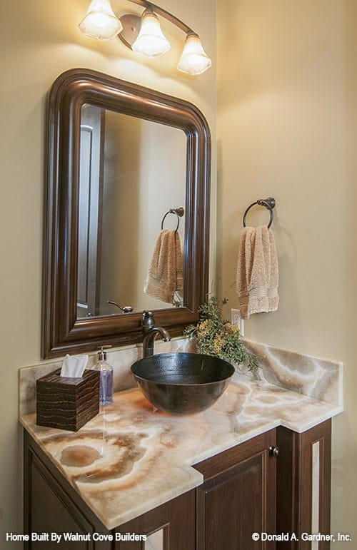 The powder room features a granite top vanity with a vessel sink, a large framed mirror, and glass sconces.