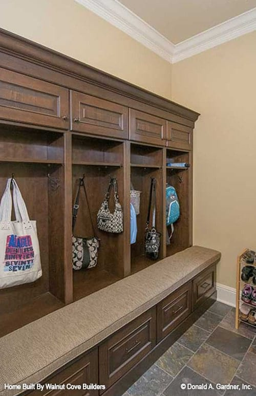 Mudroom with wooden shelves, hooks, and a cushioned bench fitted with drawers.