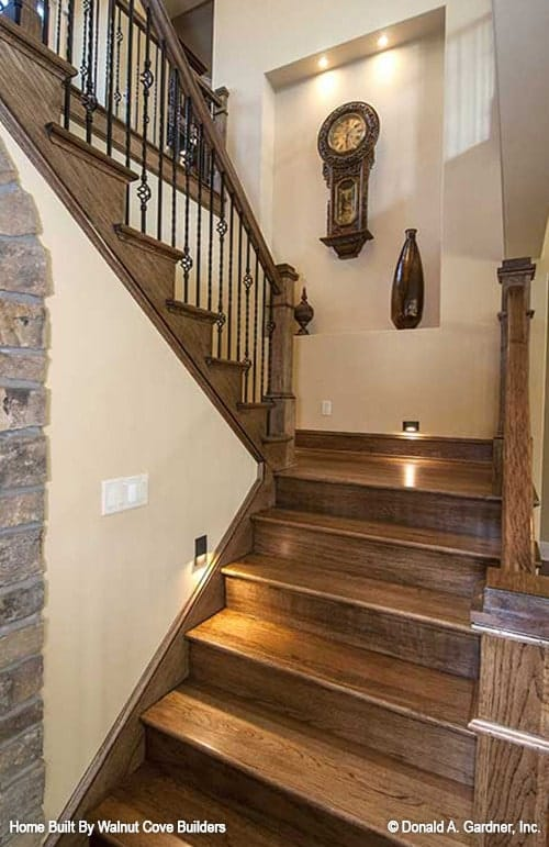 Staircase landing with an inset niche wall adorned by an antique wall clock.