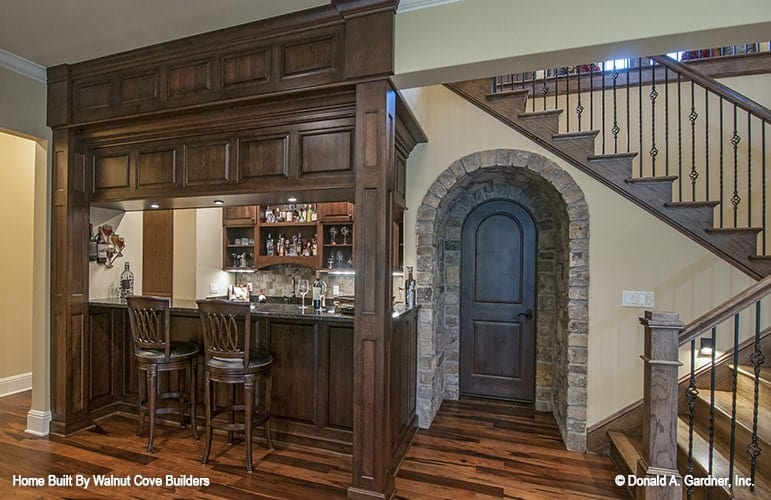 A pair of round counter chairs complement the wet bar. The arched door next to it opens to the wine cellar.