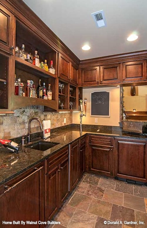 A closer look at the wet bar shows the granite countertops, wooden cabinetry, and an undermount sink.