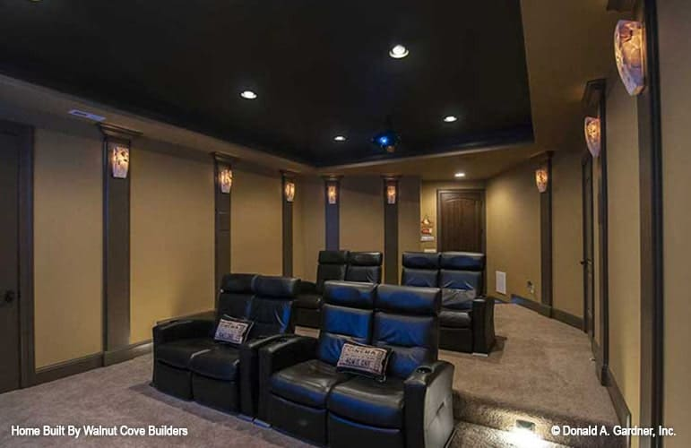Spacious media room with black recliners, a tray ceiling, and beige walls mounted with decorative sconces.