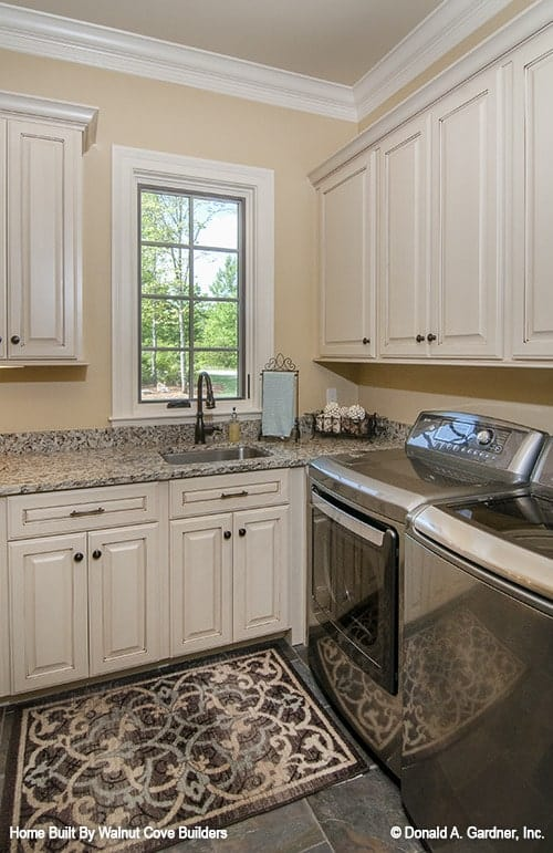 The utility room has white cabinets, top-load appliances, a granite countertop, and a patterned rug.