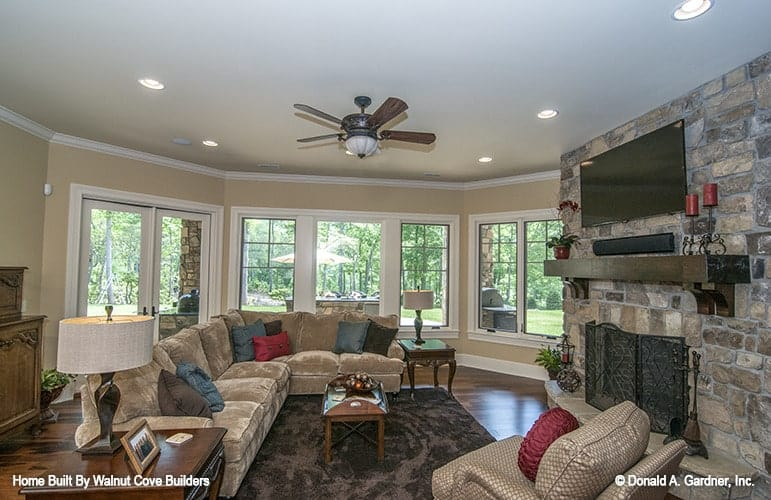 Recreation room with a fireplace, wall-mounted TV, beige seats, and a wide bay window overlooking the backyard.