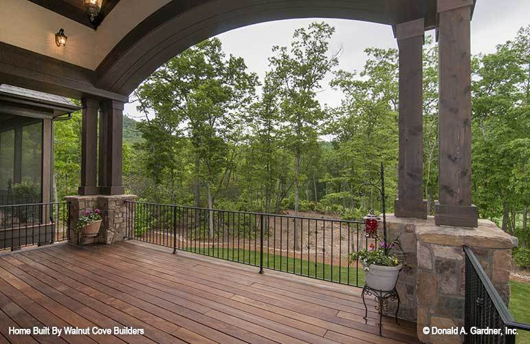 A farther view of the back porch lined with tapered columns.
