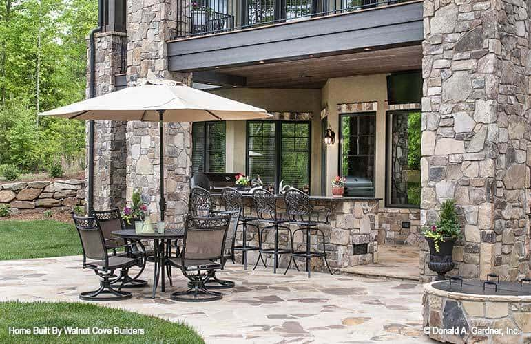 The flagstone flooring of the patio blends with the large stone pillars and bar.