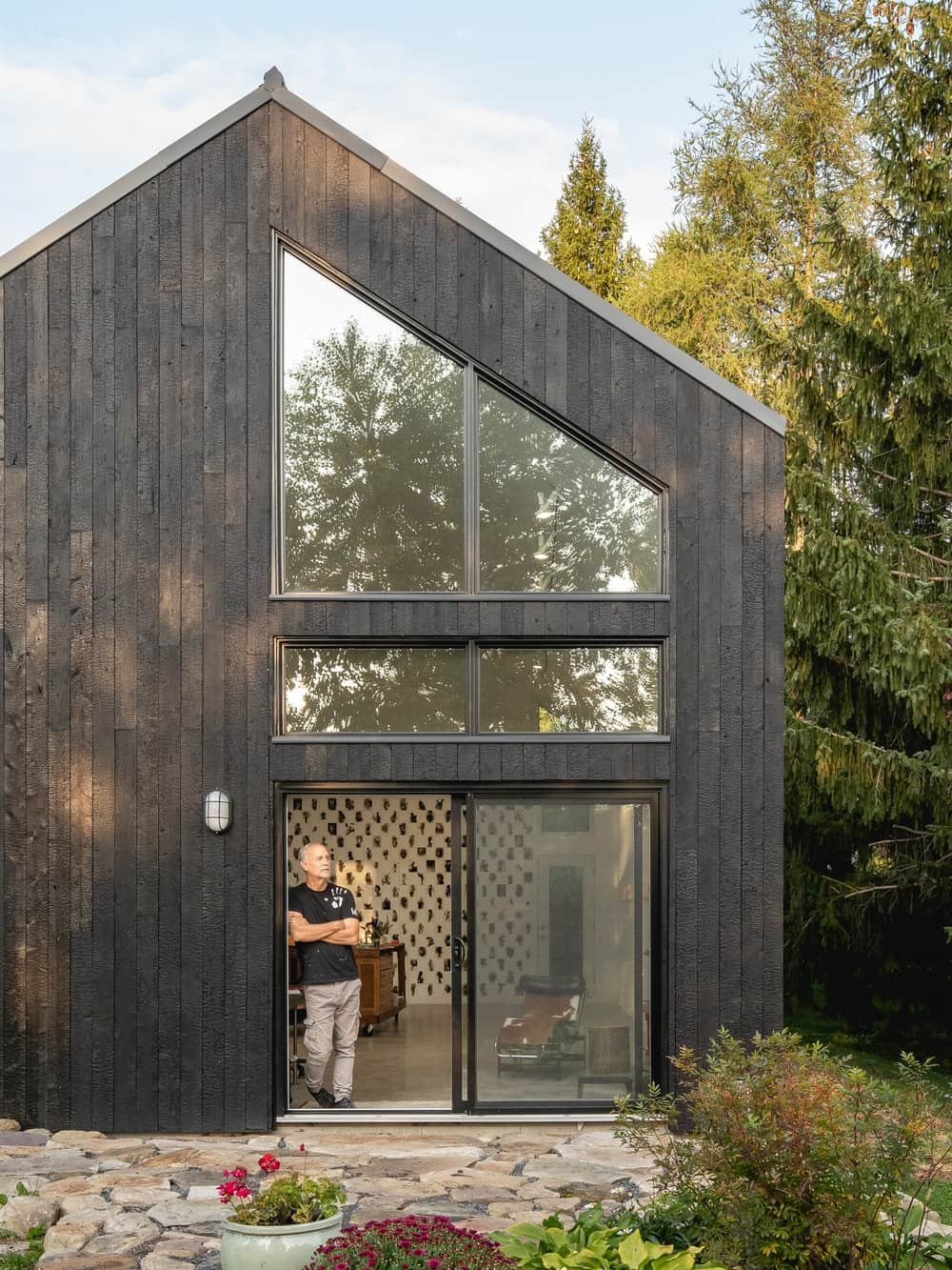 This is a close look at the house extension with dark wooden exterior walls that is complemented by the glass walls.
