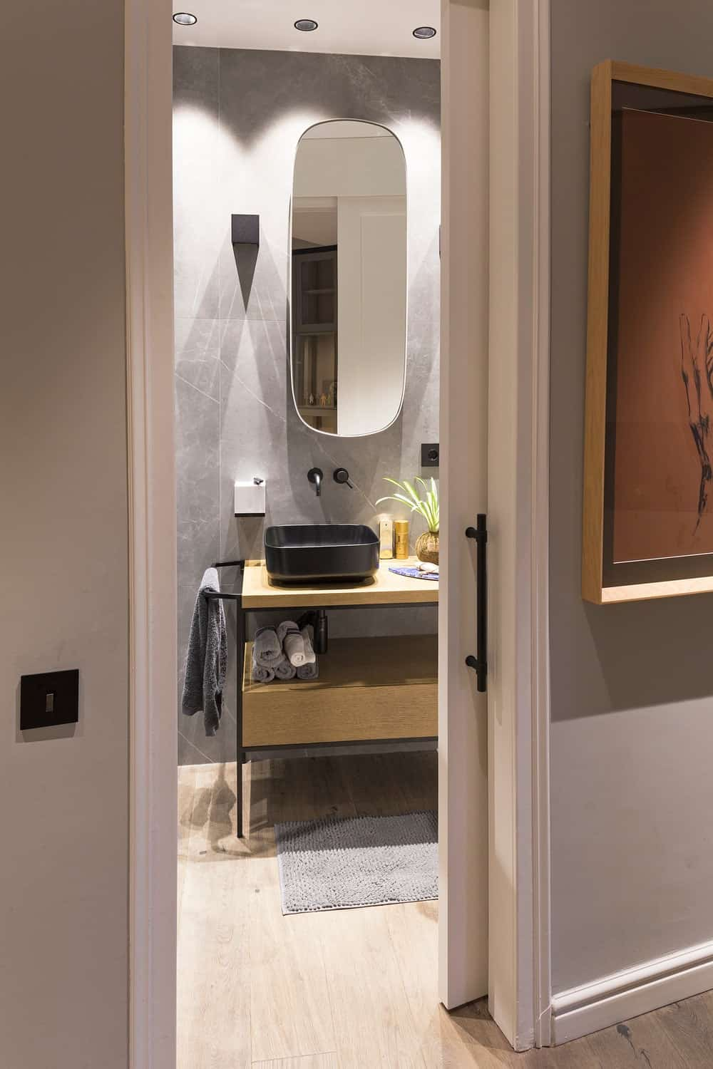 This is a view of the bathroom from the vantage of the hallway with a wooden vanity that has a dark freestanding sink.