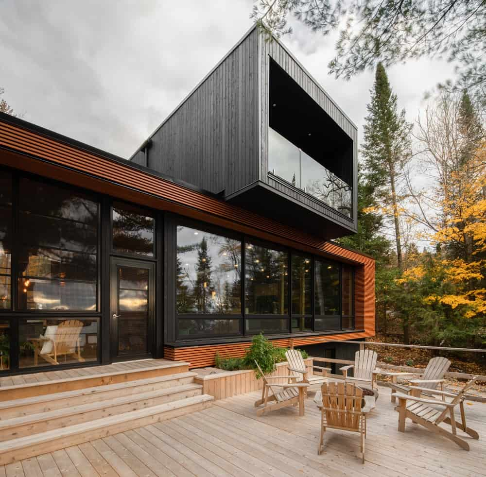 This is a look at the glass wall of the back of the house from the vantage of the large wooden deck terrace with a large area fitted with lounge chairs.