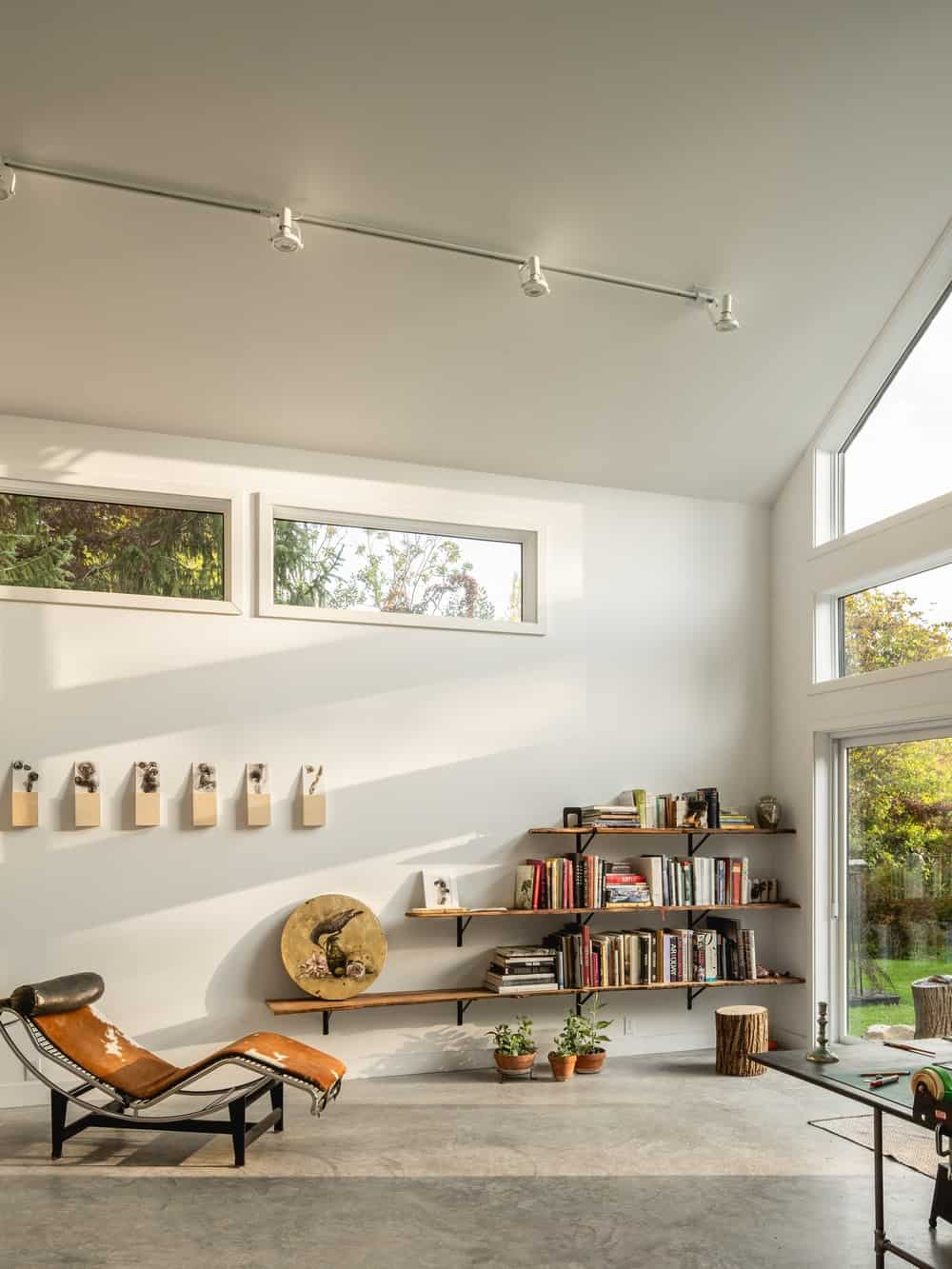 At the back of the extension is a large door that leads to the backyard by the large glass wall that illuminates the wall of shelves on the side with a lounge chair.