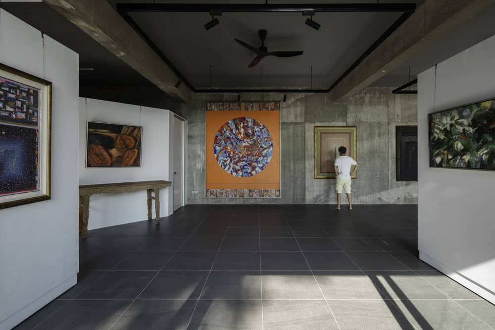 The art gallery of the house has an industrial-style look to it with gray tiles on the floor and bare concrete ceiling with modern lighting.