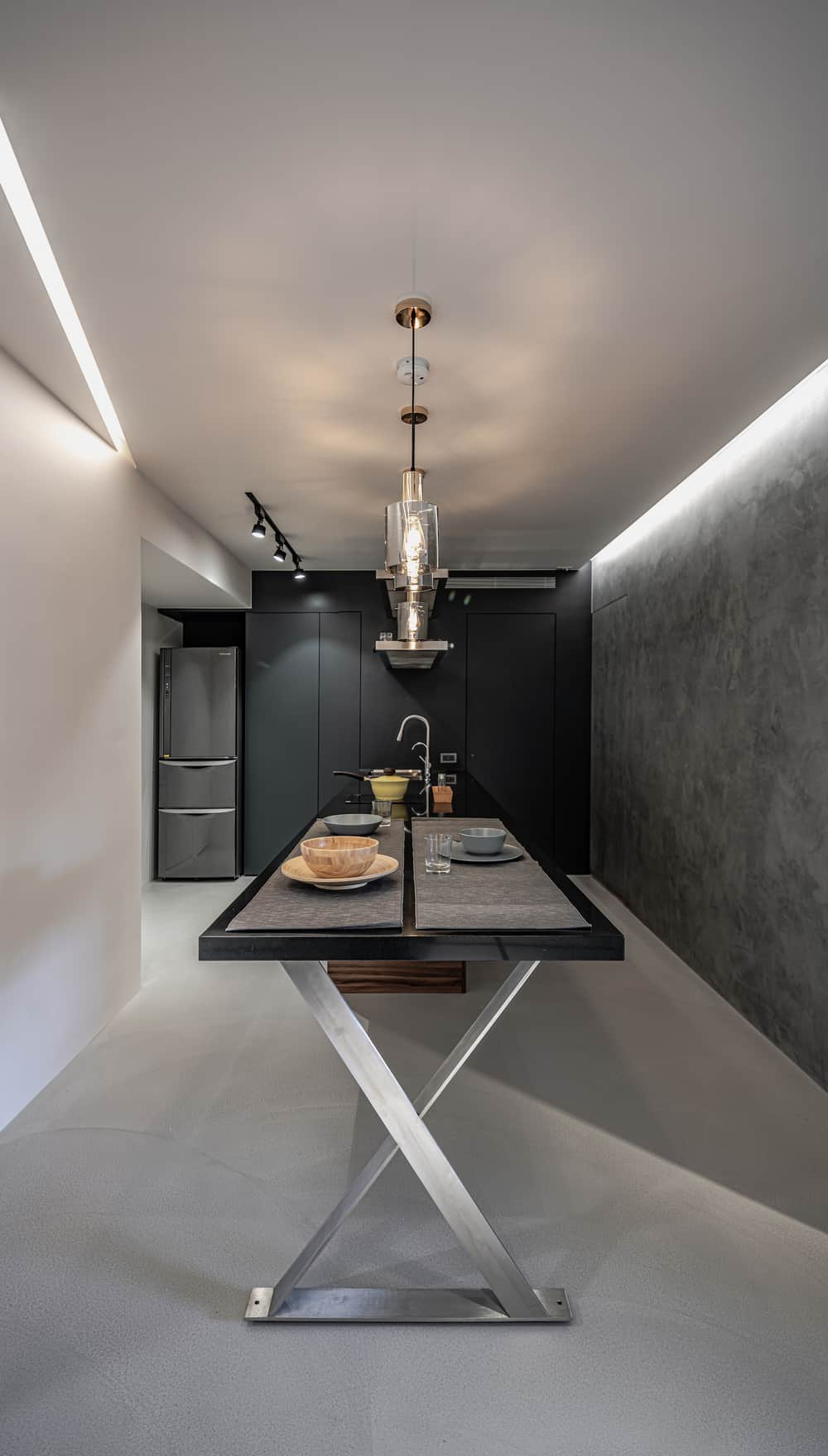 This is a view of the dining table extension of the kitchen island with a dark countertop and table top paired with silver legs and topped with pendant lights.