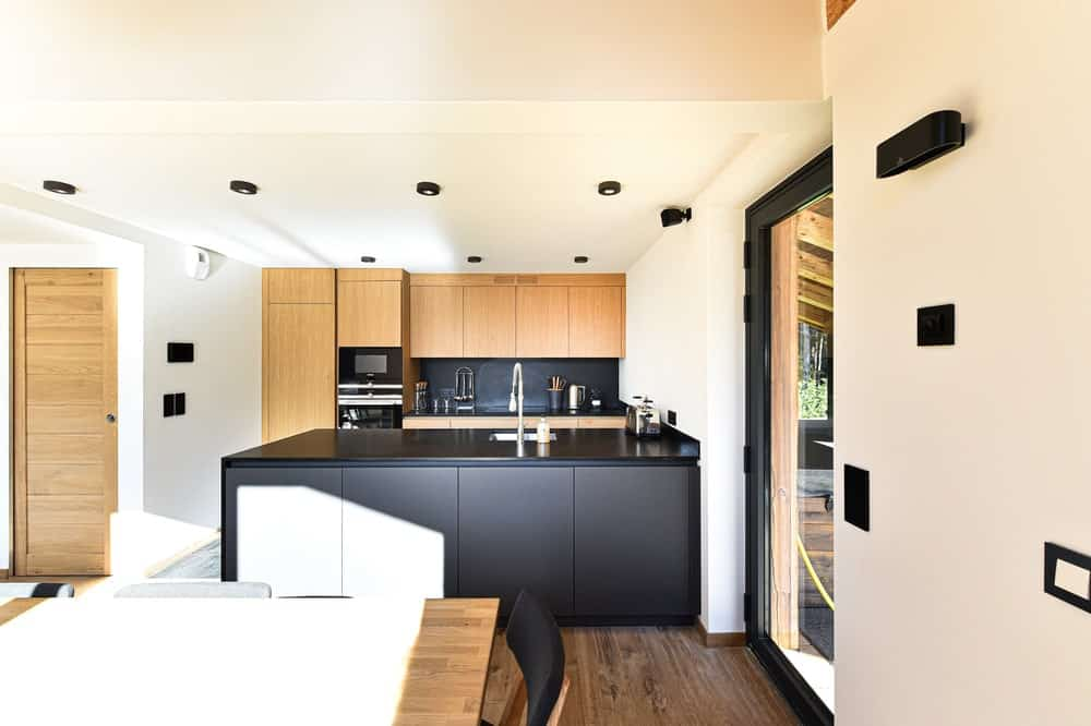 This is a look at the modern and simple kitchen with a black kitchen peninsula that stands outa gainst the white walls and ceiling.