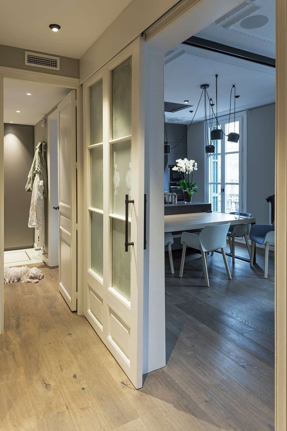 This is a view of the dining and kitchen from the hallway with a sliding French door that matches well with the ceiling.