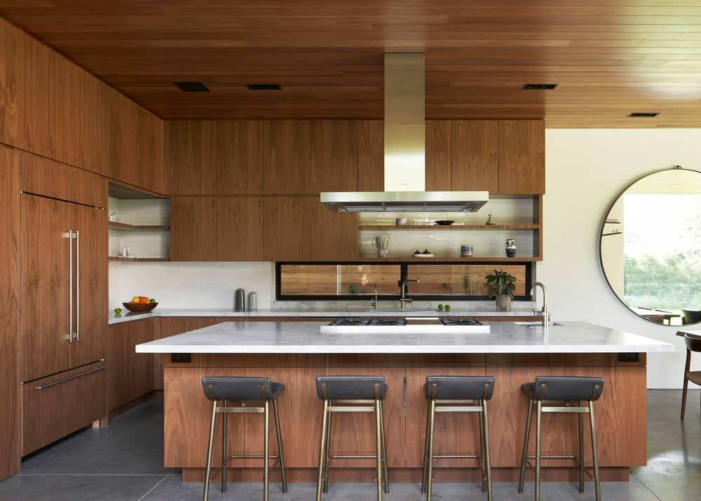 The kitchen has wooden elements on its ceiling, cabinetry and the large kitchen island. These make the countertops and stainless steel appliances stand out.