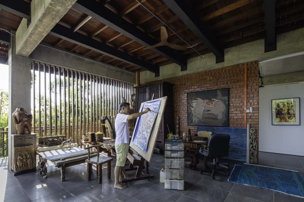 This is the art studio with lots of natural light, open space for painting and a large brick wall on the far side.