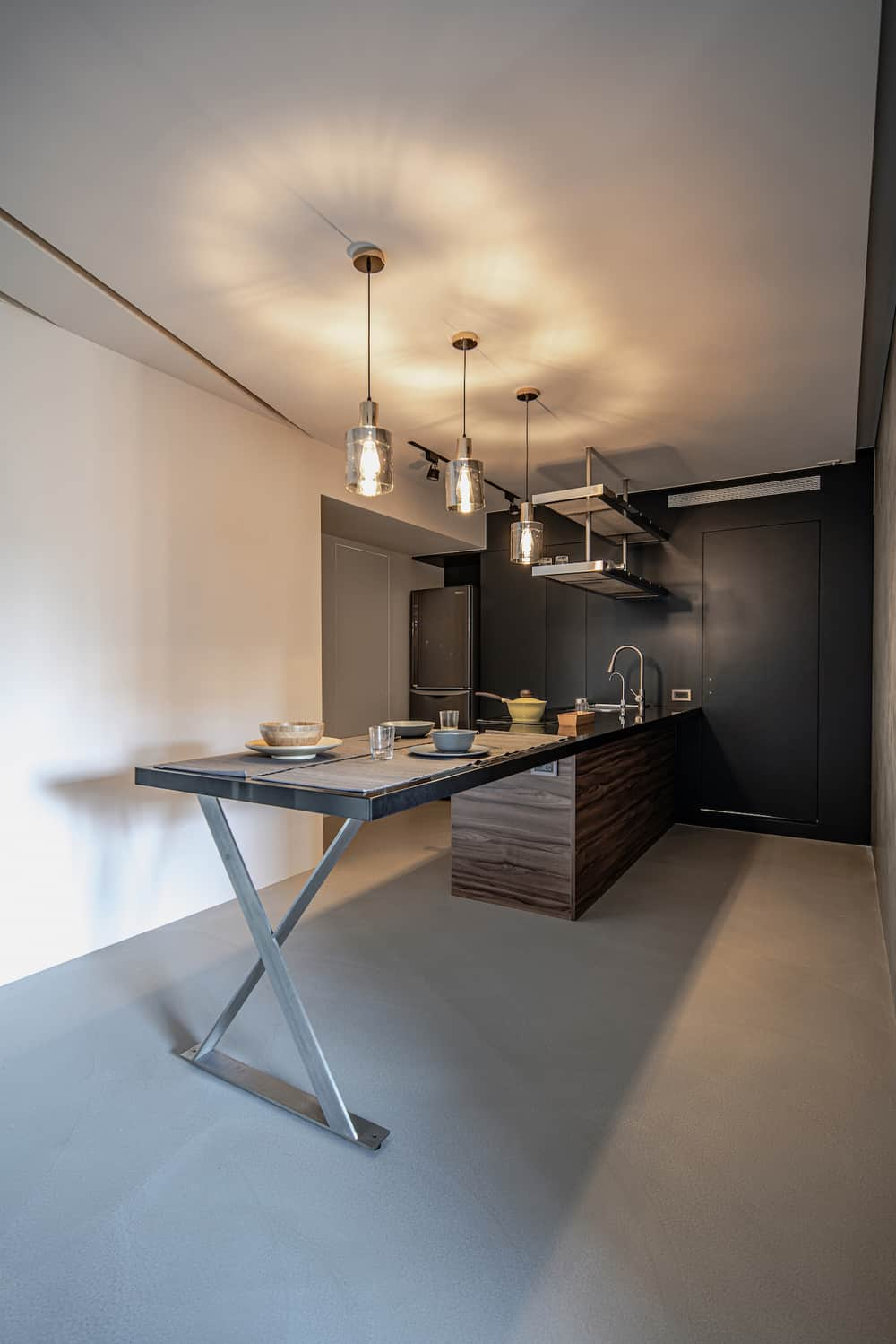 This is a side view of the large kitchen island with a set of modern cabinetry at the far end that has a black tone that makes the stainless steel fridge stand out.