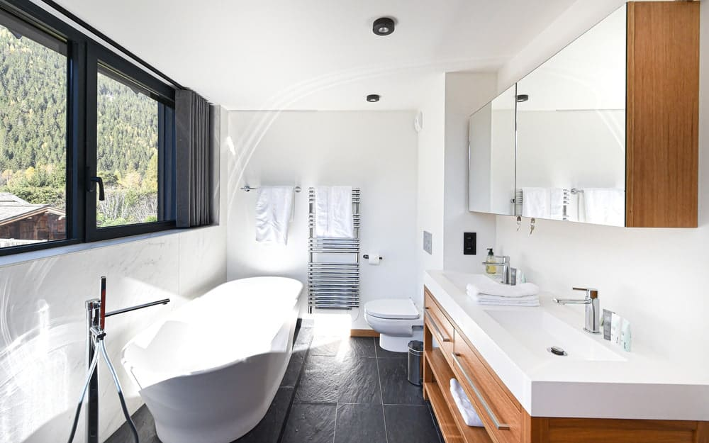 The bathroom has a large freestanding bathtub across from the vanity contrasted by the dark flooring.