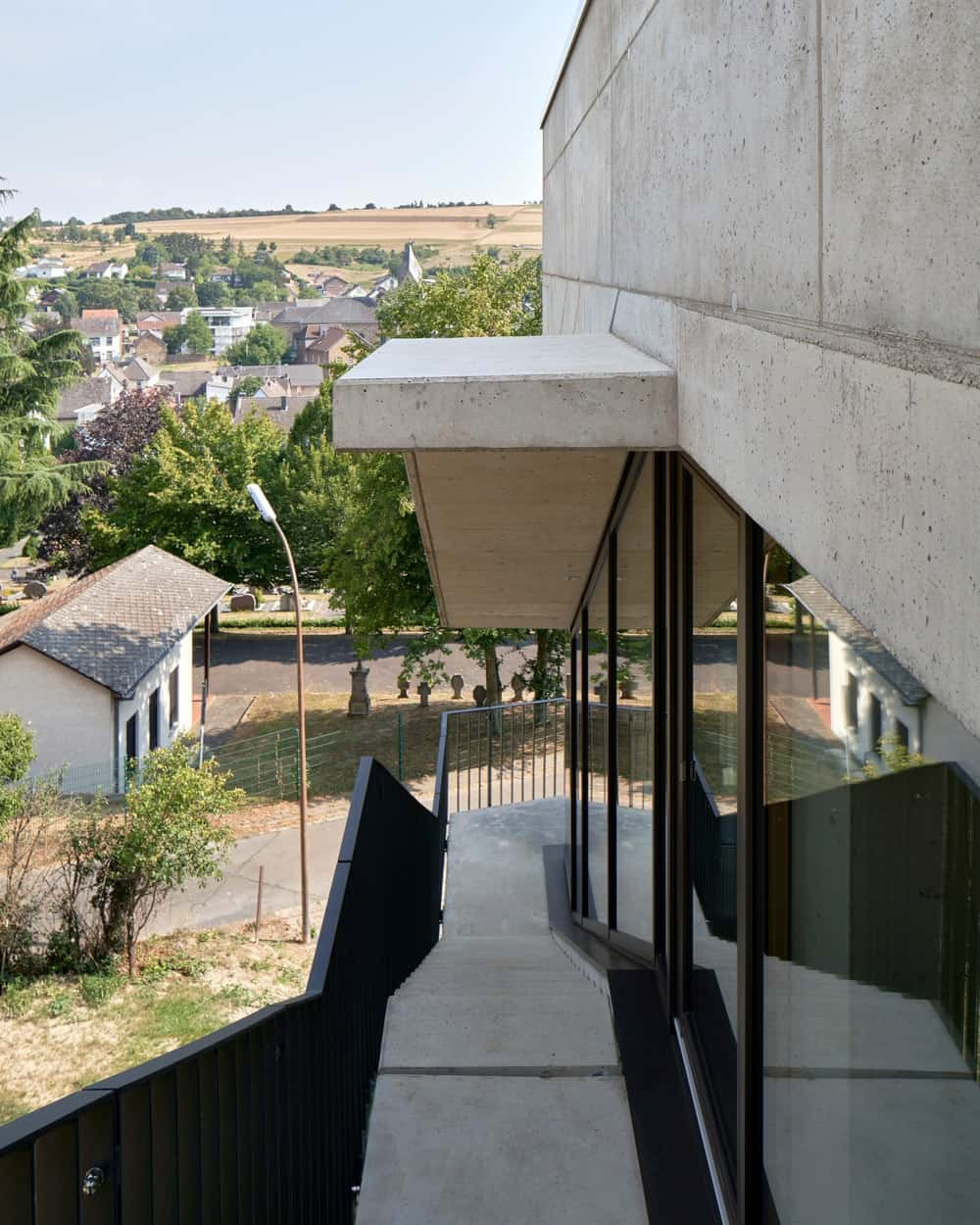 The balcony leads to this outdoor staircase that is still followed by glass walls.