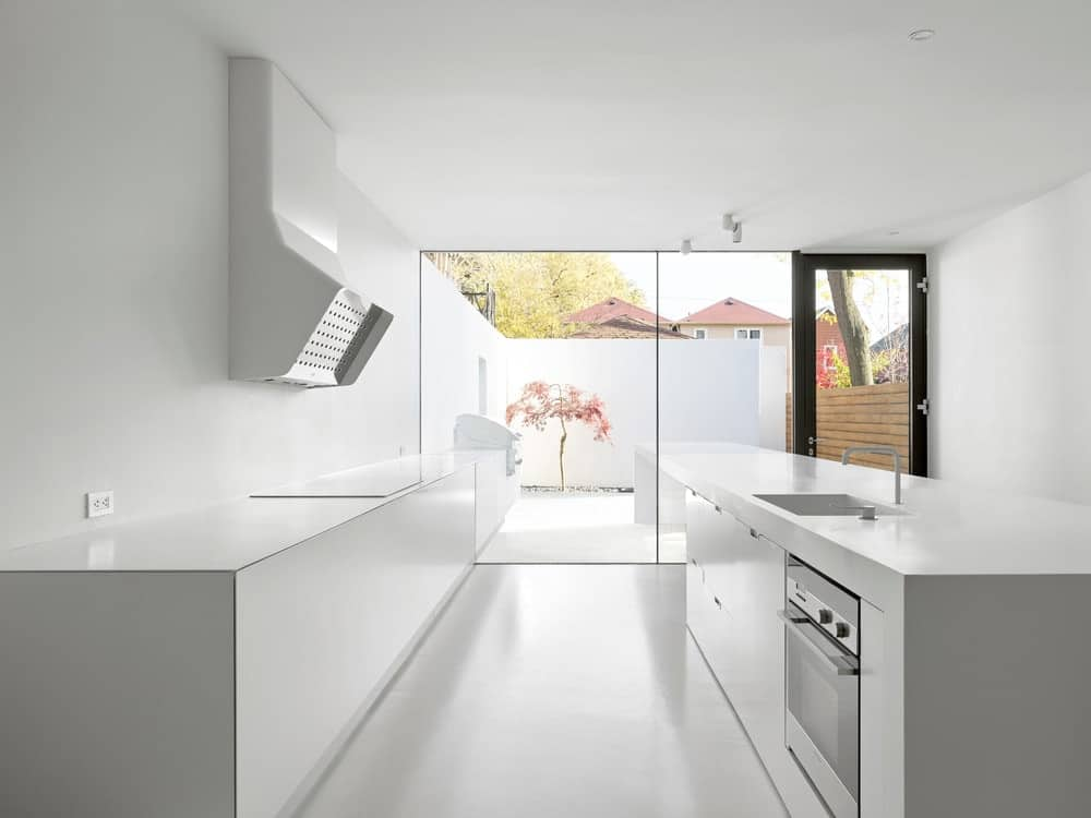 This is the kitchen with a consistent white tone that is complemented by the natural lighting coming from the glass walls on the far side.