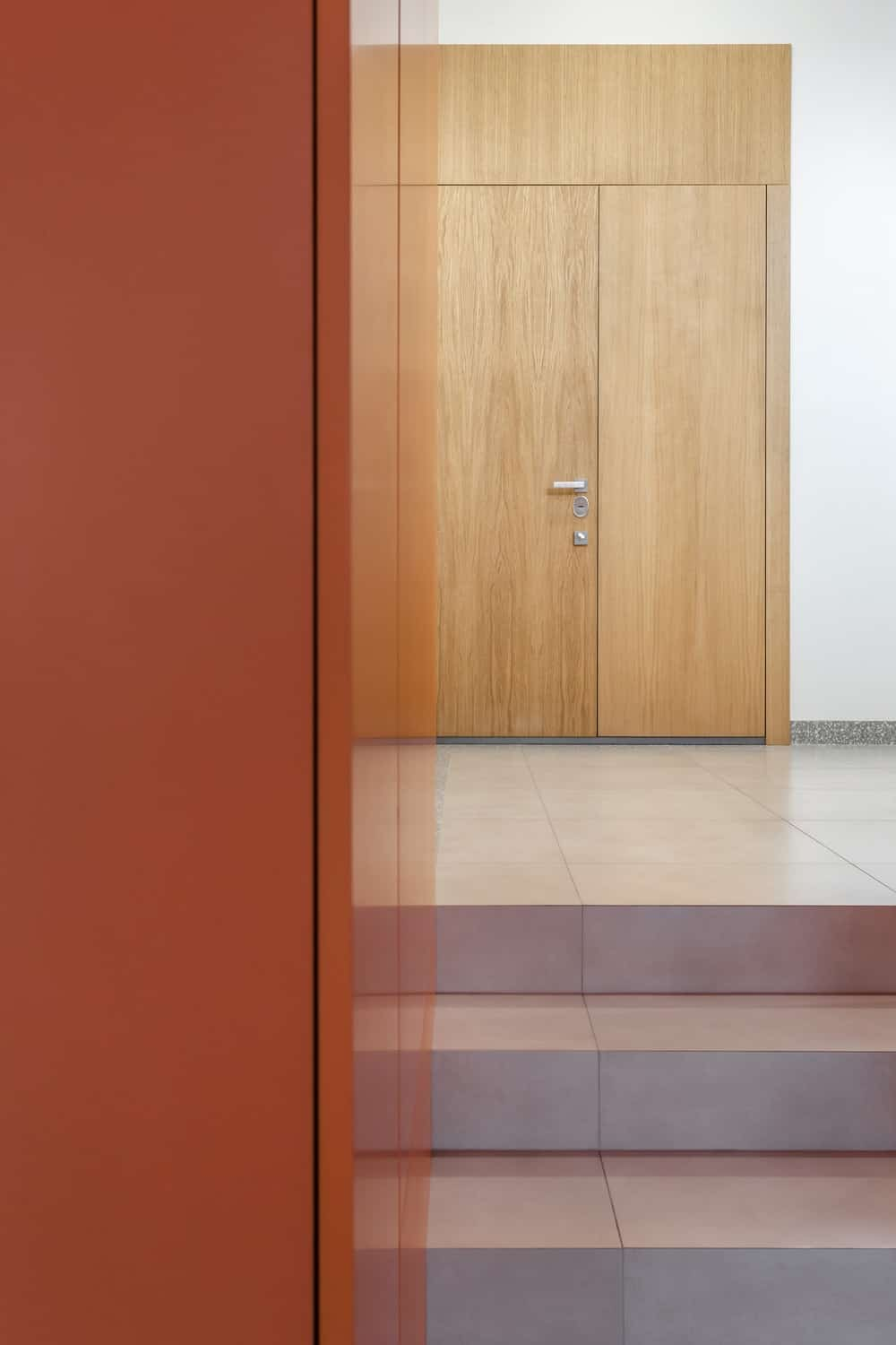 Upon entry of the house, you are welcomed by this simple foyer with a wide wooden main door.