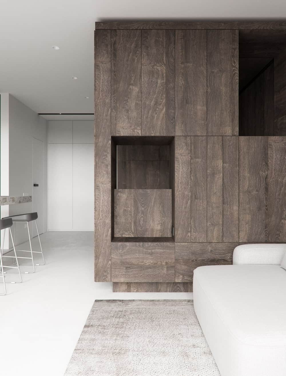The wooden structure of the bedroom also serves as a shelving and wooden cabinetry of the living room.