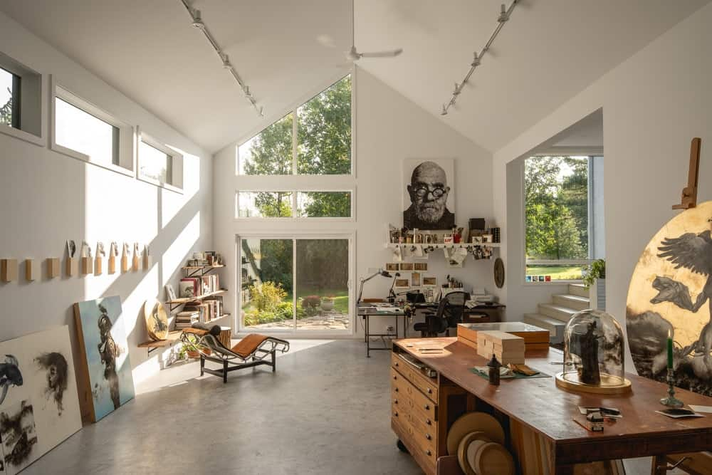 This is the spacious and airy interiors of the art studio with a tall cathedral ceiling and white walls.