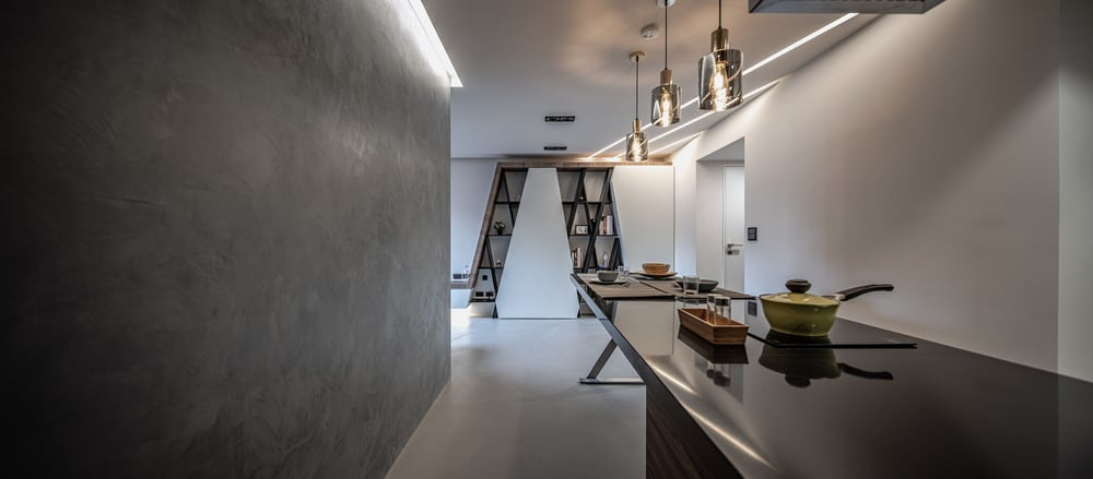 This view shows that the large and sleek dark dining table connects to the kitchen island that houses the cooking area.