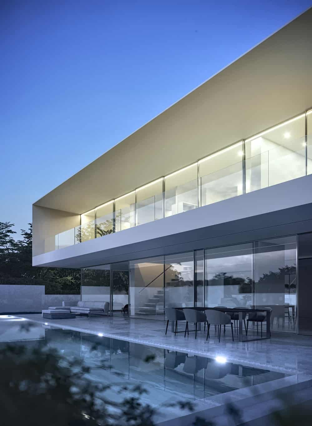 When the lights of the ground level are out, the glass walls of the house hides the interiors and acts as a mirror.