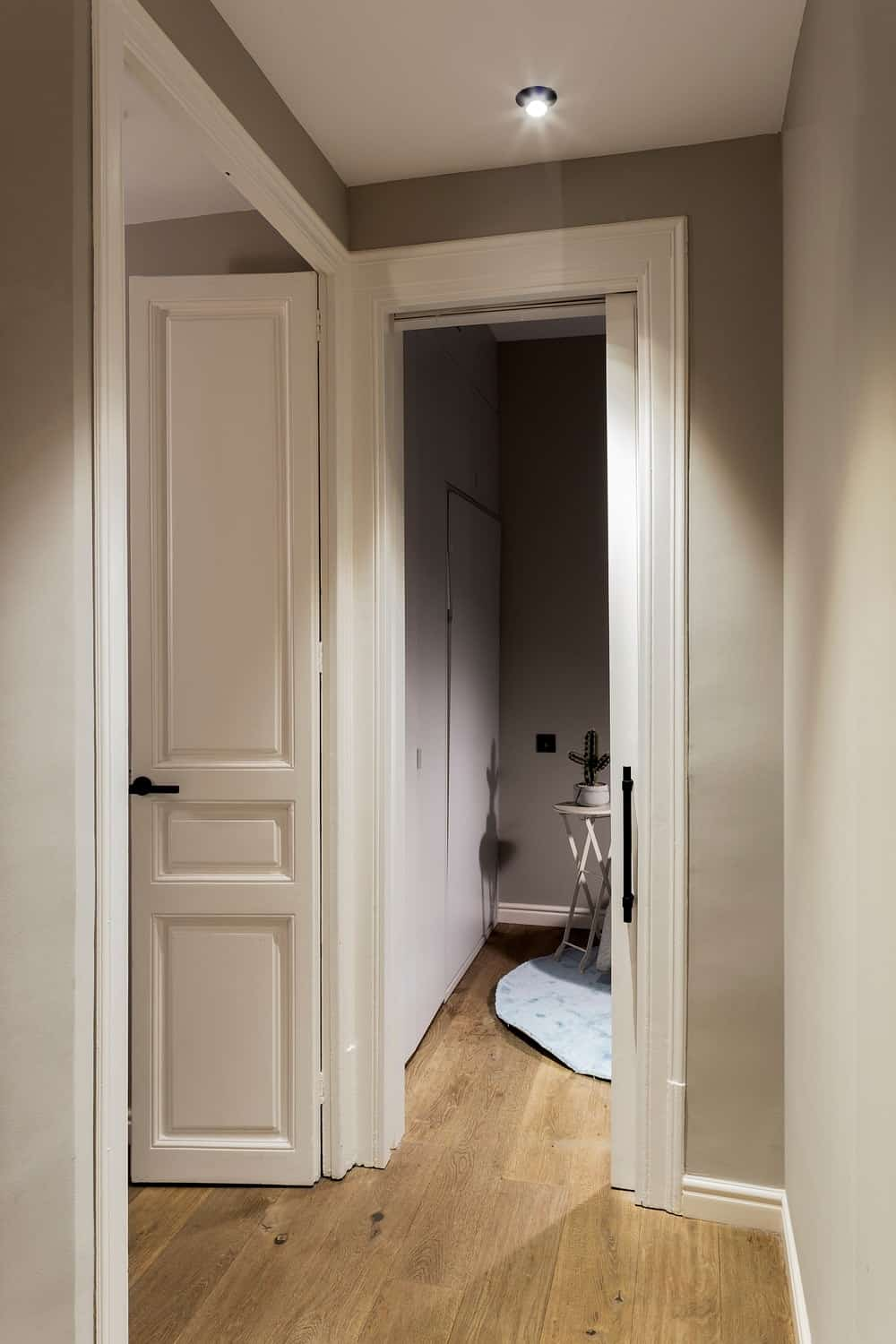 This view of the hallway shows the narrow doorway towards the home office.