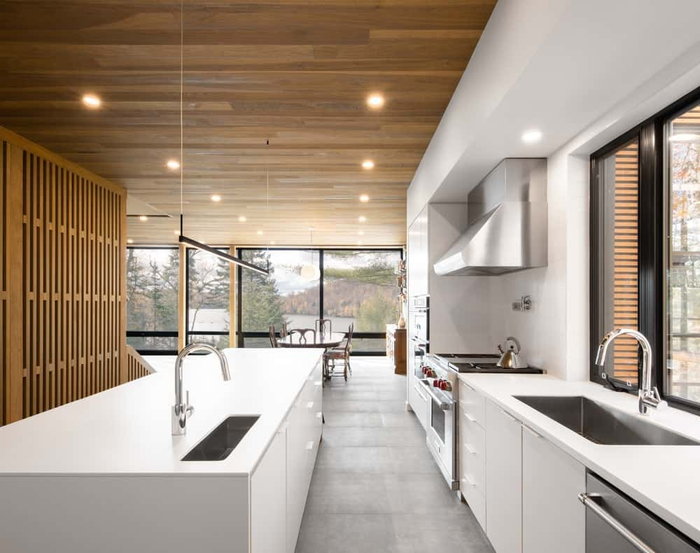 This is the bright and white kitchen that stands out against the wooden tone of the walls and ceiling with recessed lights over the cabinetry.